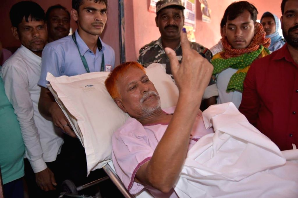 A patient who arrived in an ambulance, shows his forefinger marked with indelible ink after casting vote during the last phase of 2019 Lok Sabha polls, in patna, on May 19, 2019.