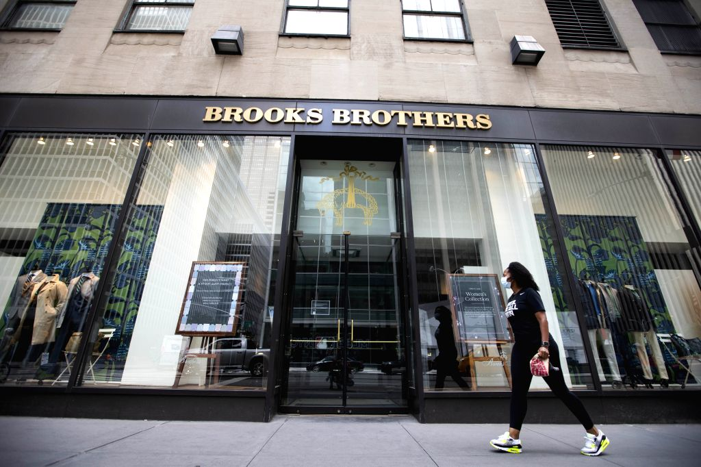 A pedestrian walks past a Brooks Brothers retail store in Manhattan of New York, the United States, July 8, 2020. Brooks Brothers, one of the oldest apparel ...