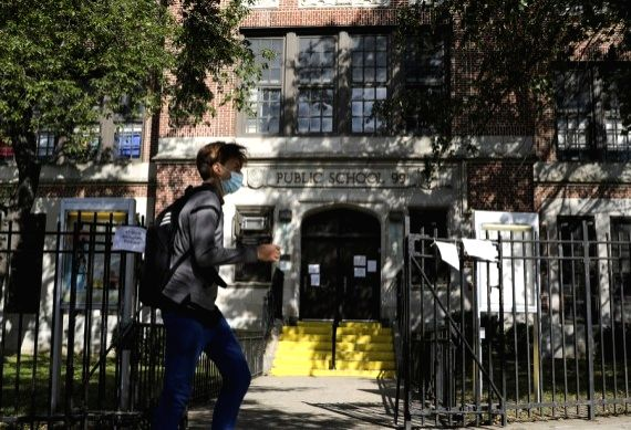 A pedestrian walks past a public school in Kew Gardens, one of the COVID-19 hotspot areas in New York City, the United States. (Xinhua/Wang Ying/IANS)