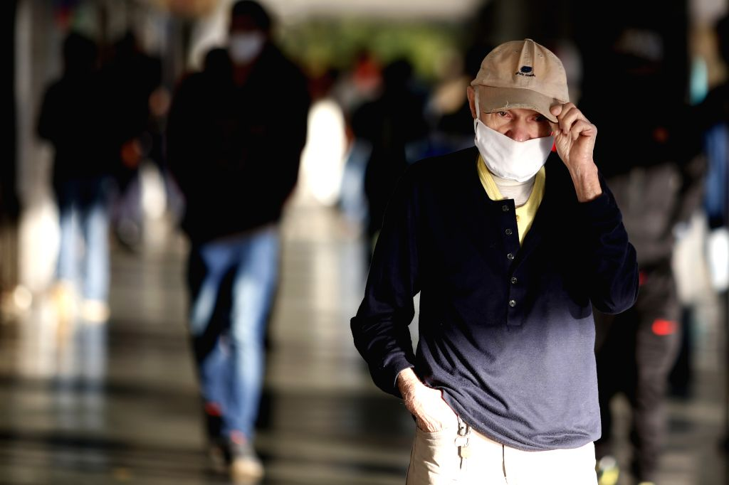 A pedestrian wearing a face mask is seen on a street in Brasilia, Brazil, Aug. 7, 2020.