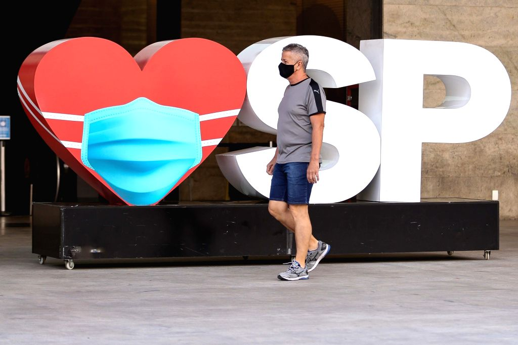 A pedestrian wearing a face mask walks on the street in Sao Paulo, Brazil, Aug. 12, 2020.   Brazil on Wednesday said it registered 1,175 deaths from the novel ...