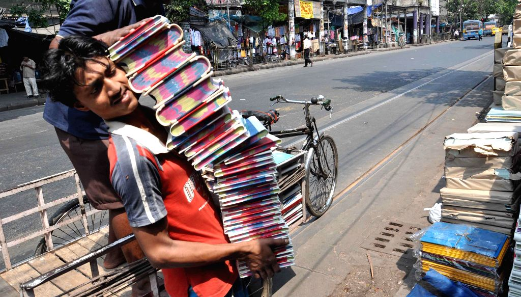 A person carries 'halkhata'  or registers used for accounting purposes in shops ahead of Bengali New Year, as some Hindu businessmen follow Bengali year as their accounting year, in Kolkata on April .