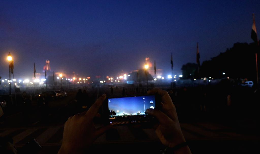 A person clicks an illuminated view of the North and South Block ahead of the Beating Retreat ceremony in New Delhi on Jan 27, 2018.