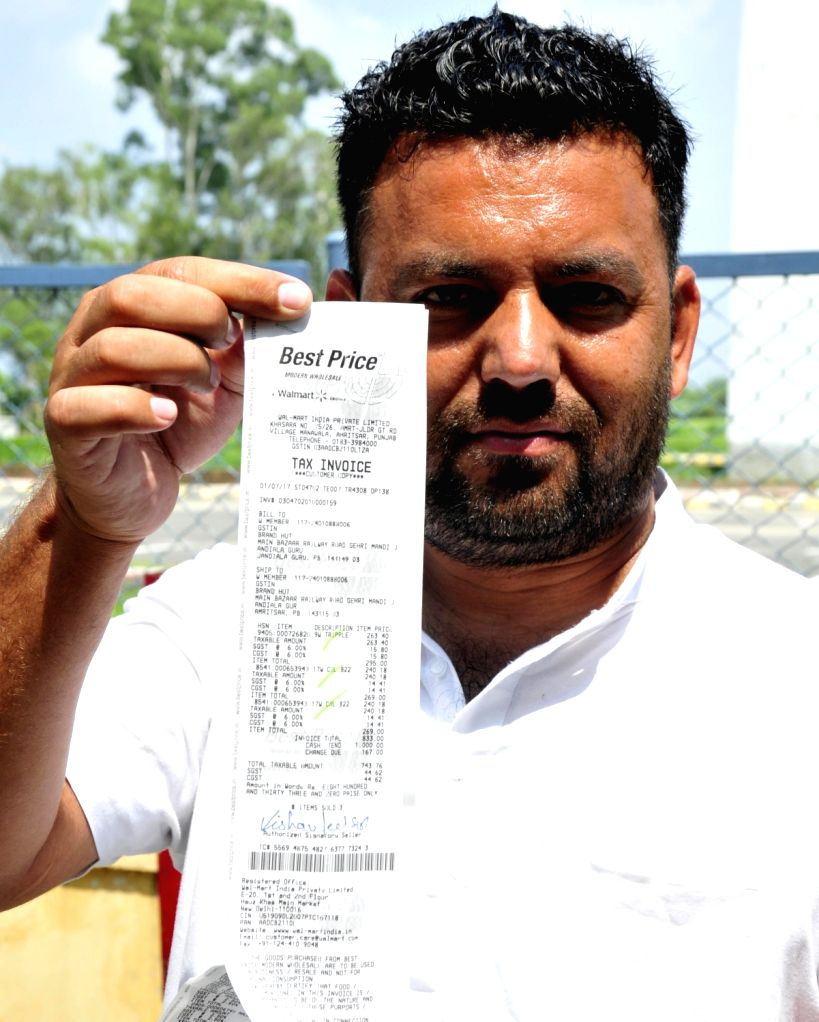 A person displays a bill with the newly implemented Goods and Services Tax (GST) in Amritsar on July 1, 2017.
