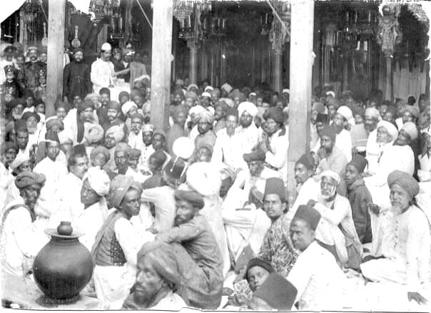 A photo of Mir Babar Ali \'Anis\' (on chair, top left) reciting a marsiya in Hyderabad in the early 1870s