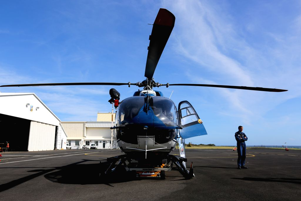 A pilot stands near a helicopter taking part in the searching mission at an airport in Saint Denis, La Reunion, Aug. 14, 2015. The administrator of Reunion ...