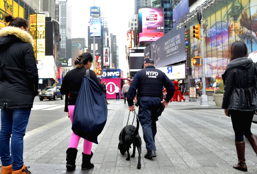A police officer patrols with a police dog in the Times Square in Manhattan, New York City, the United States, Nov. 19, 2015. New York City officials and the ...