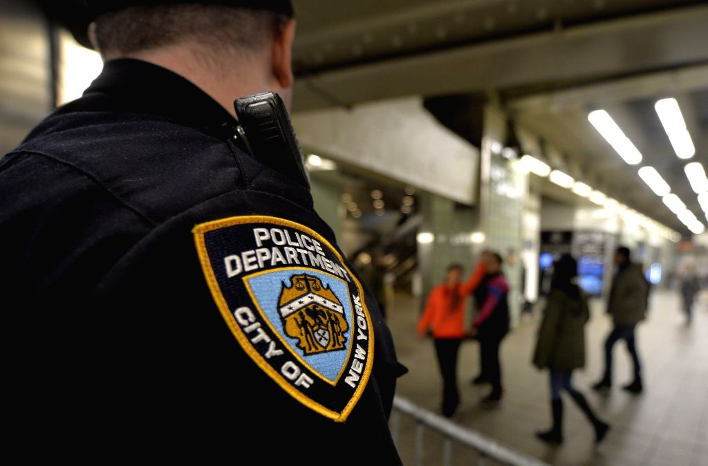 A police officer stand guard at a subway station near the Times Square in Manhattan, New York City, the United States, Nov. 19, 2015. New York City officials and ...