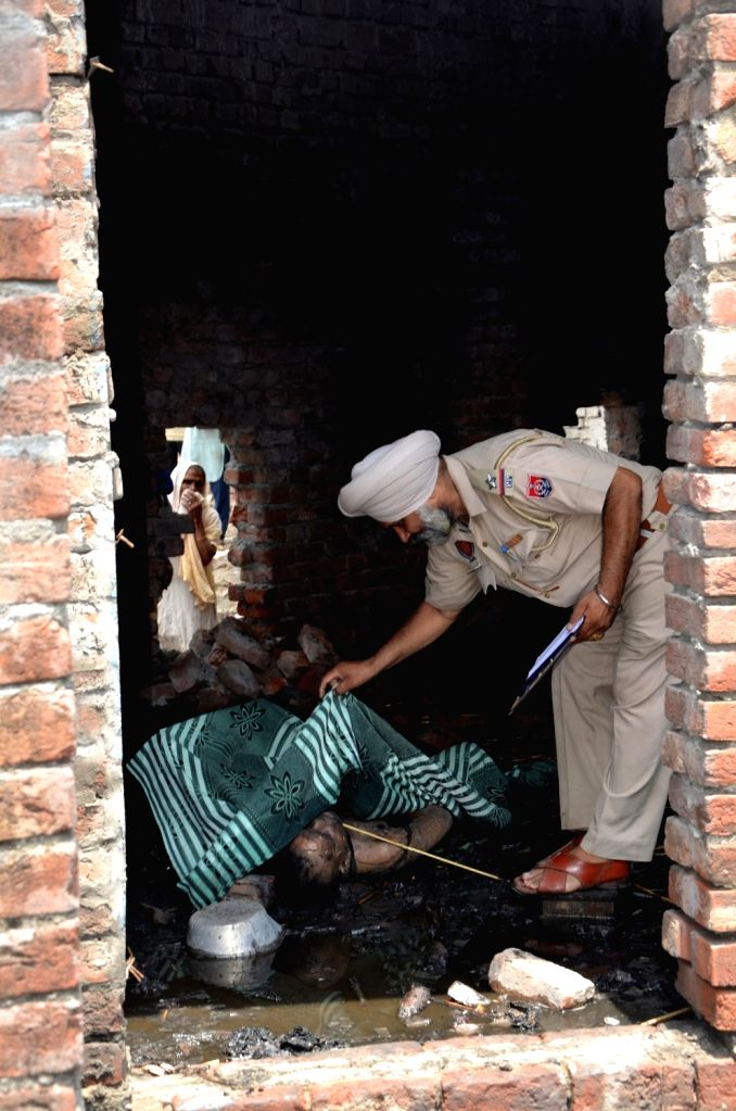 A police personnel inspects a body at the fireworks manufacturing unit that caught fire, in Amritsar on May 30, 2018.