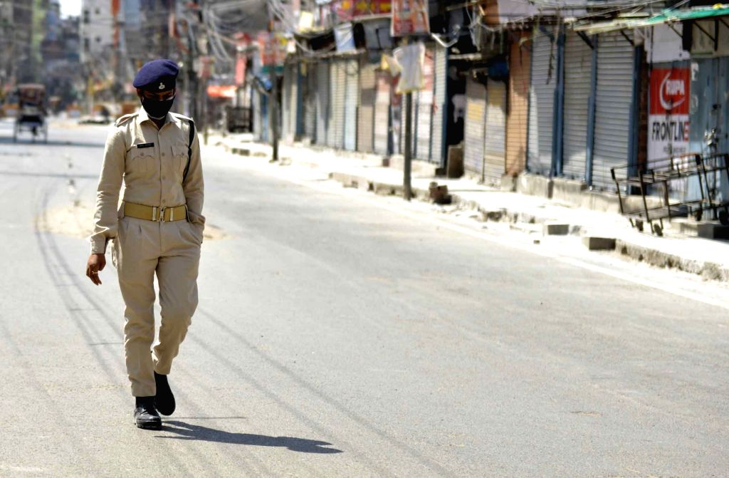 A police personnel passes by the deserted Hathwa Market during the 21-day nationwide lockdown imposed as a precautionary measure to contain the spread of coronavirus, in Patna on Apr 1, 2020.