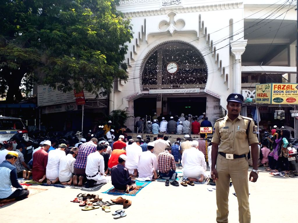 A police personnel stands guard as devotees offer prayers on the first Friday of Ramadan at Badi Masjid, Mallepally in Hyderabad, on May 10, 2019.