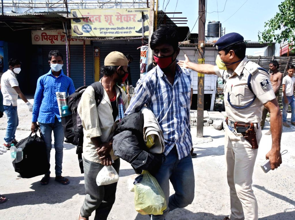 A police personnel takes migrant workers to a relief camp on Day 7 of the 21-day nationwide lockdown imposed as a measure to contain the spread of  coronavirus, in Patna on March 31, 2020.