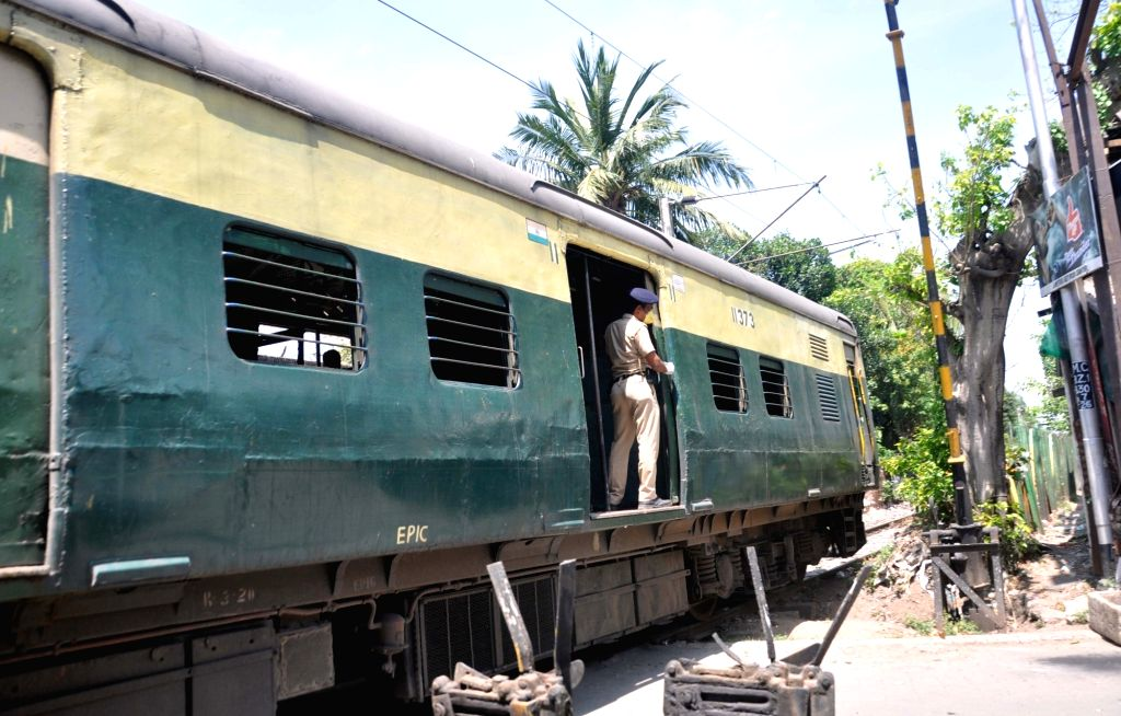 A police personnel travels in a local train running as part of emergency railway services for the prviders of essential commodities and services during the 21-day nationwide lockdown ...