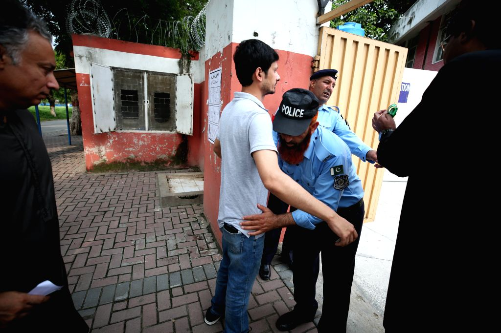 :A policeman checks a voter outside a polling station in Islamabad, capital of Pakistan, on July 25, 2018. Pakistanis started casting votes in the ...