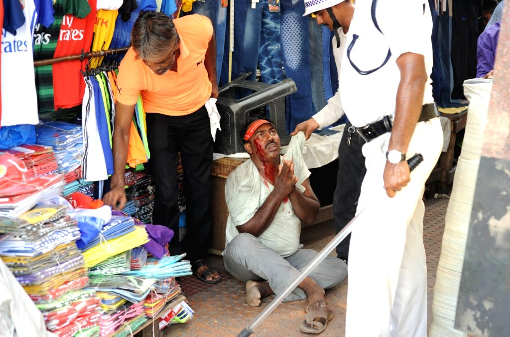 A policeman offers handkerchief to one of the injured protesters who clashed with police after a number of Left Front MLAs including its legislature party leader Sujan Chakraborty were ... - Sujan Chakraborty