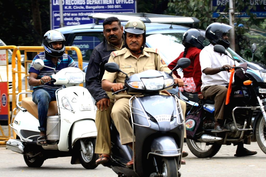 A policeman riding pillion on a scooter ignoring the new helmet rule, that mandates that all riders and their pillions have to compulsorily wear the protective headgear, in Bengaluru, on ...