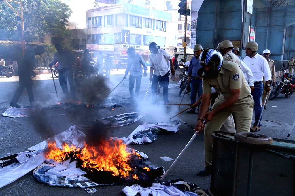 "A policeman tries to douse fire lit by the members of Patidar Anamat Andolan Samiti (PAAS) during ""Jail Bharo Andolan"" in Surat of Gujarat on April 17, 2016."