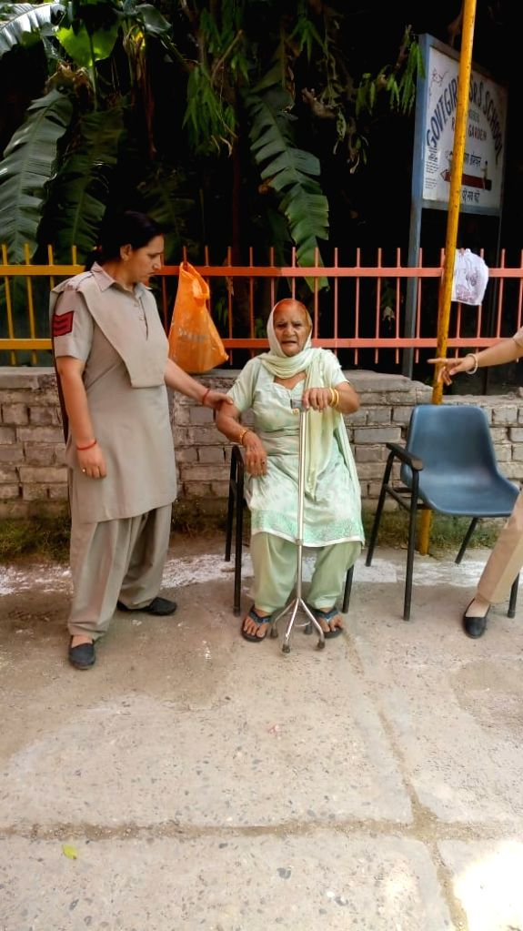 A policewoman assists an elderly lady who arrived to cast her vote during the sixth phase of 2019 Lok Sabha elections, in Delhi's Prashant Vihar on May 12, 2019.