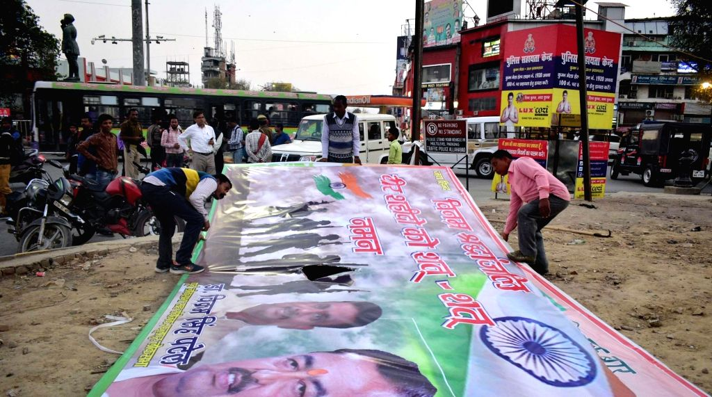 A political hoarding being removed after the Model Code of Conduct came into effect following the announcement of the Lok Sabha election schedule by the Election Commission, in Prayagraj ... - Code