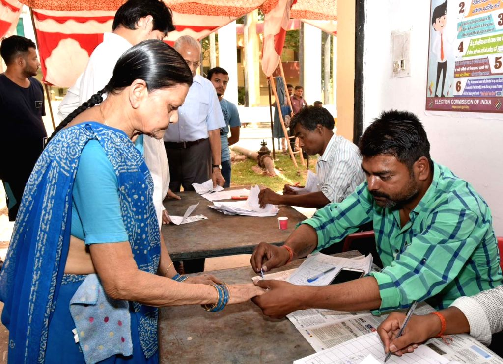 A polling official administers indelible ink to a voter, at a polling booth, during the sixth phase of 2019 Lok Sabha elections, in Prayagraj on May 12, 2019.