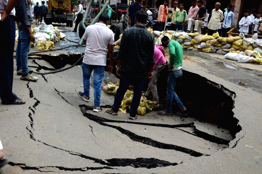 A portion of a road caves in at Ghat Gate Bazar after heavy rains lashed Jaipur on July 23, 2018.