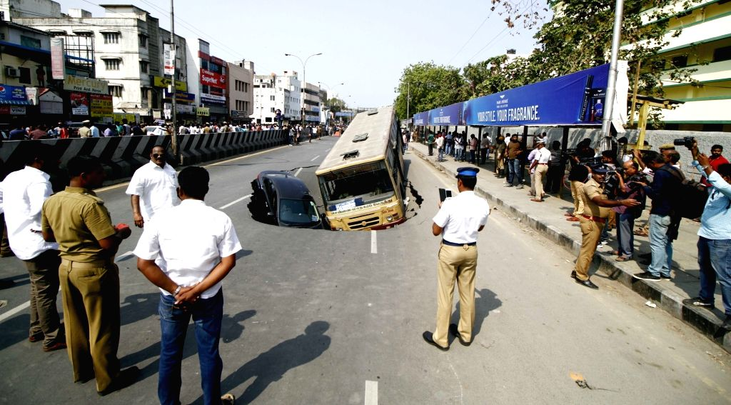 A portion of a road caves in near the Thousand Lights mosque trapping a car and a bus in Chennai 0n April 9, 2017.