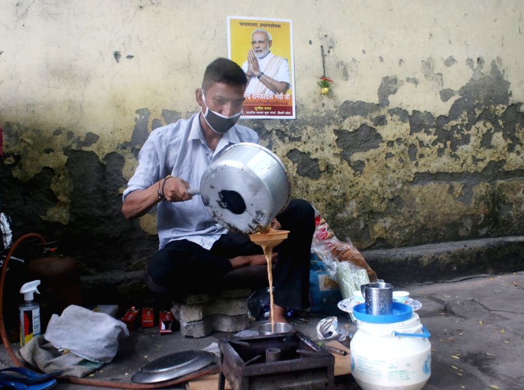 "A poster of Prime Minister Narendra Modi that reads ""Shri Narendra Damodardas Modi Ji - #ChaiwalaPradhanSewak"" comes up at a wall behind a tea stall where a man is busy preparing ... - Narendra Modi"