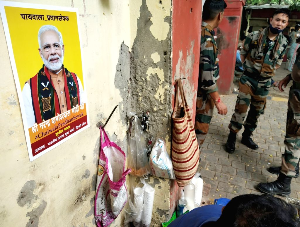 "A poster of Prime Minister Narendra Modi that reads ""Shri Narendra Damodardas Modi Ji - #ChaiwalaPradhanSewak"" comes up at a wall behind a tea stall ahead of his birthday, in New ... - Narendra Modi"