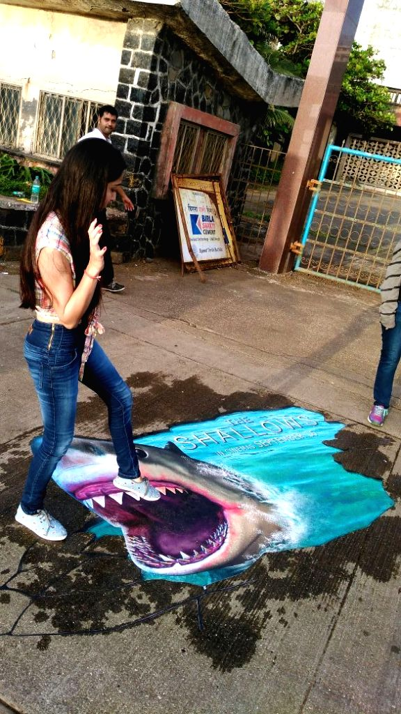 "A pothole in Mumbai painted with a shark face as a promotional initiative for ""The Shallows\""."