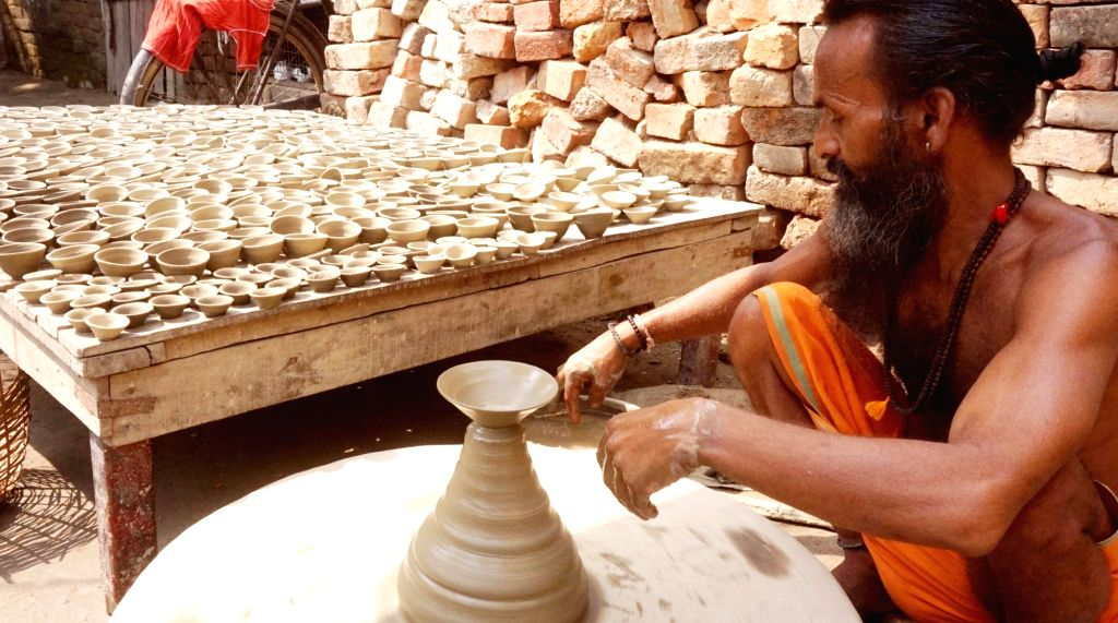 A potter busy making earthen lamps ahead of Diwali - festival of lights in Varanasi, on Oct 14, 2017.