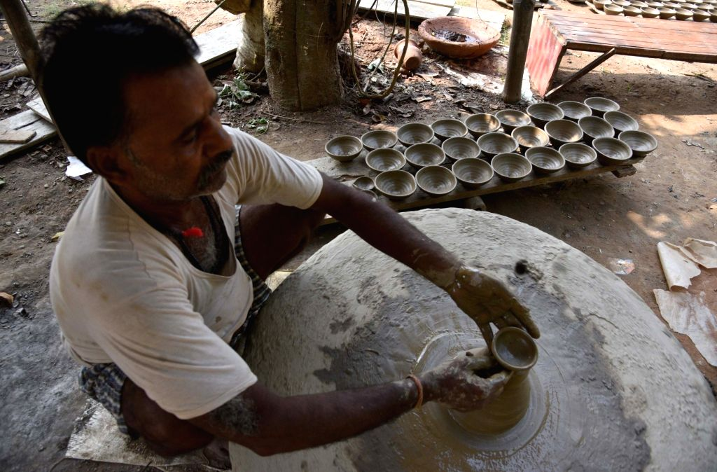 A potter busy making earthen lamps ahead of Diwali - festival of lights in Guwahati on Oct 15, 2017.