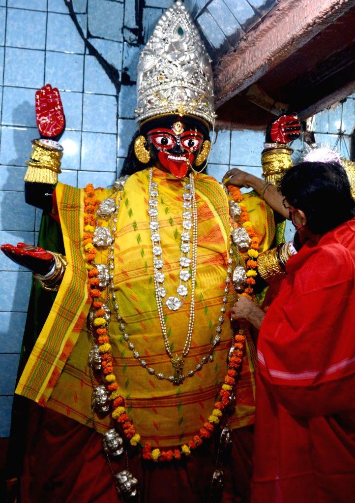 A priest adorns an idol of Goddess Kali with beautiful ornaments at Firingi KaliBari on the eve of Kali Puja, in Kolkata on Nov 13, 2020.