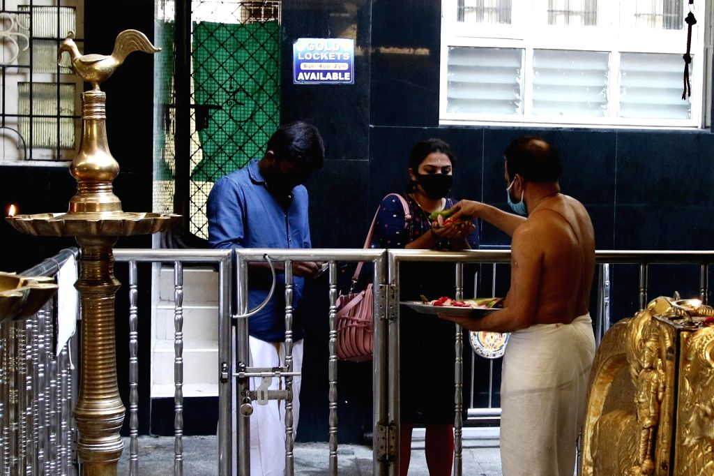 A priest offers prasadam to the devotees at a temple that reopened after the Tamil Nadu Government permitted the reopening of the places of worship as part of several relaxations that shall ...