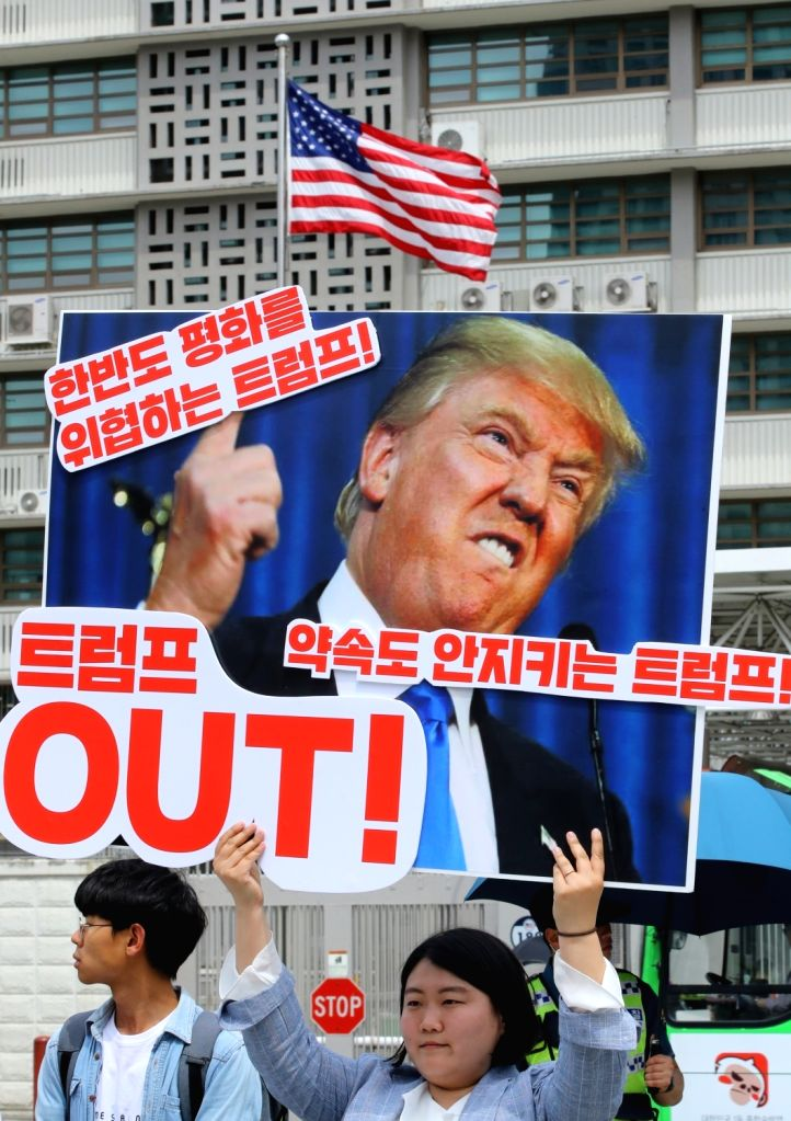 """A protester holds a banner that says, """"Trump jeopardizes peace on the Korean Peninsula,"""" during a rally in front of the U.S. Embassy in Seoul on May 25, 2018, to criticize the U.S. ..."""