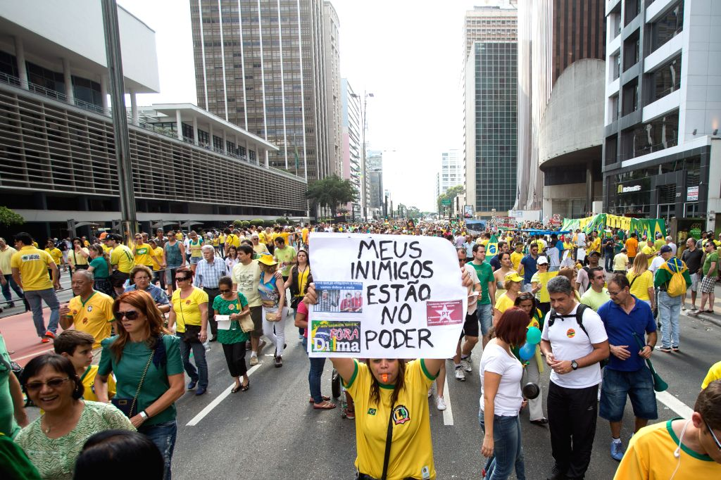 """A protester holds a cardboard with the slogan """"my enemies are in power"""" during an anti-government demonstration in Sao Paulo, Brazil, Aug. 16, 2015. A ..."""