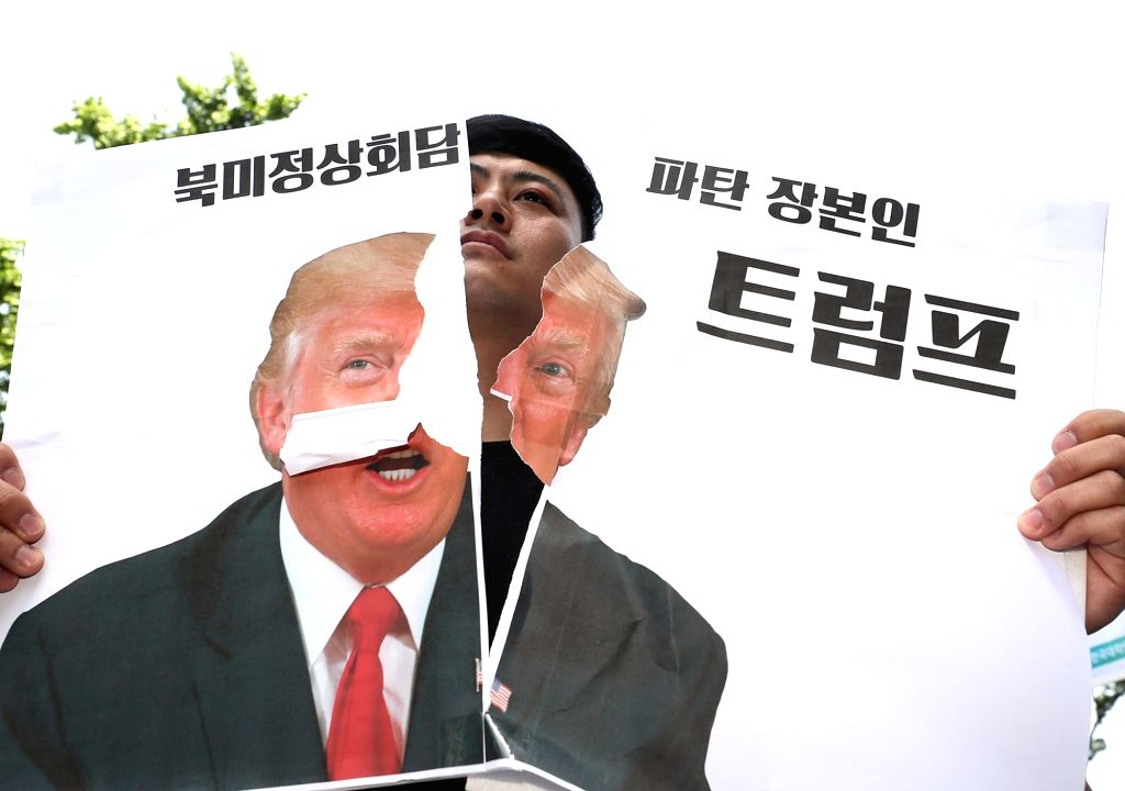 A protester tears a picture of U.S. President Donald Trump during a rally in front of the U.S. Embassy in Seoul on May 25, 2018, to criticize the U.S. government and call for a summit with ...