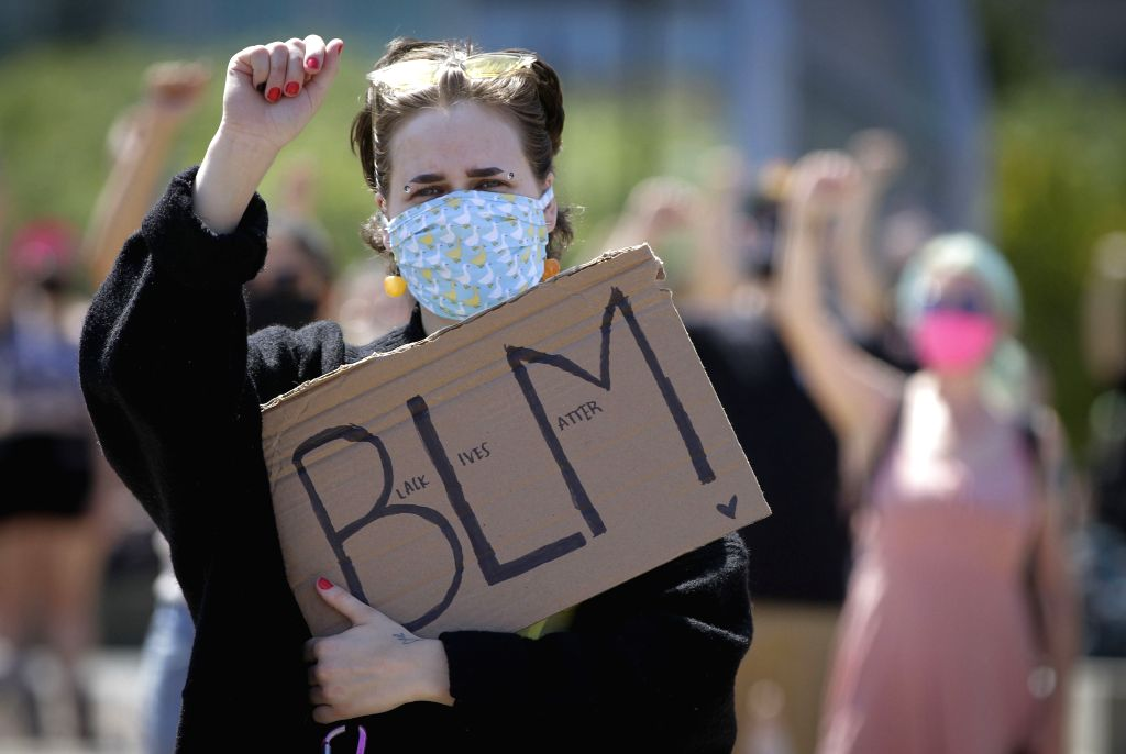 A protestor carries a sign while participating in the Emancipation Day march in Vancouver, British Columbia, Canada, August 1, 2020. In conjunction with the ...