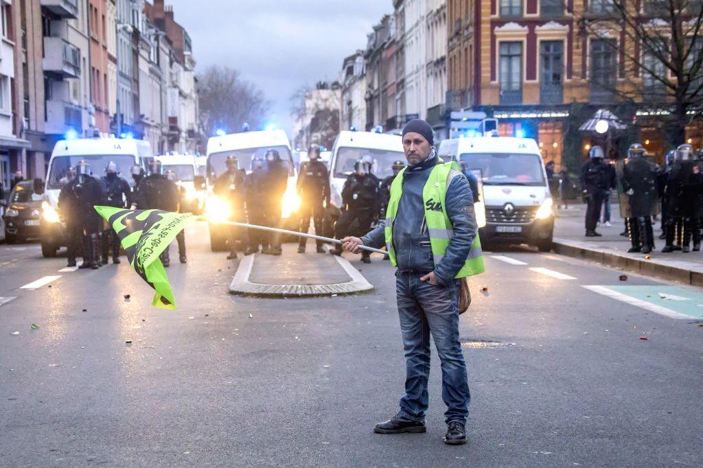 A protestor confronts policemen during a demonstration against pension reform in Lille, north France, Jan. 9, 2020. France's transport strike against President ...