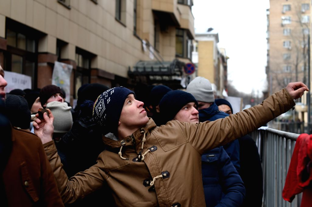 A protestor throws a rock towards Turkey embassy in Moscow as it was attacked during a protest against the downing of a Russian warplane by Turkey, in Moscow, ...