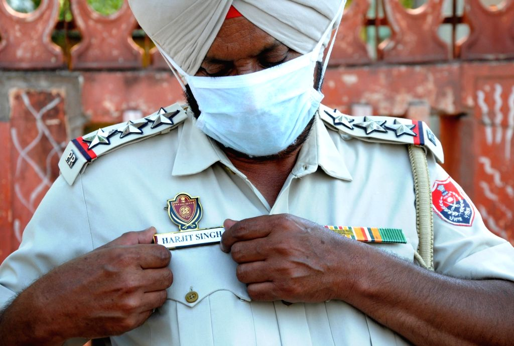 A Punjab police personnel wears the name of ASI Harjeet Singh on his badge, whose hand was chopped off in clashes between the police and the Nihang Sikhs in Patiala; as a gesture to honour ... - Harjeet Singh