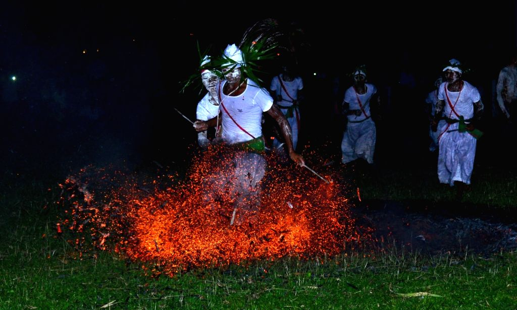 A Rabha priest walks on burning charcoal during Baikho festival in Assam in Hahim in Kamrup district of the state on June 5, 2016.