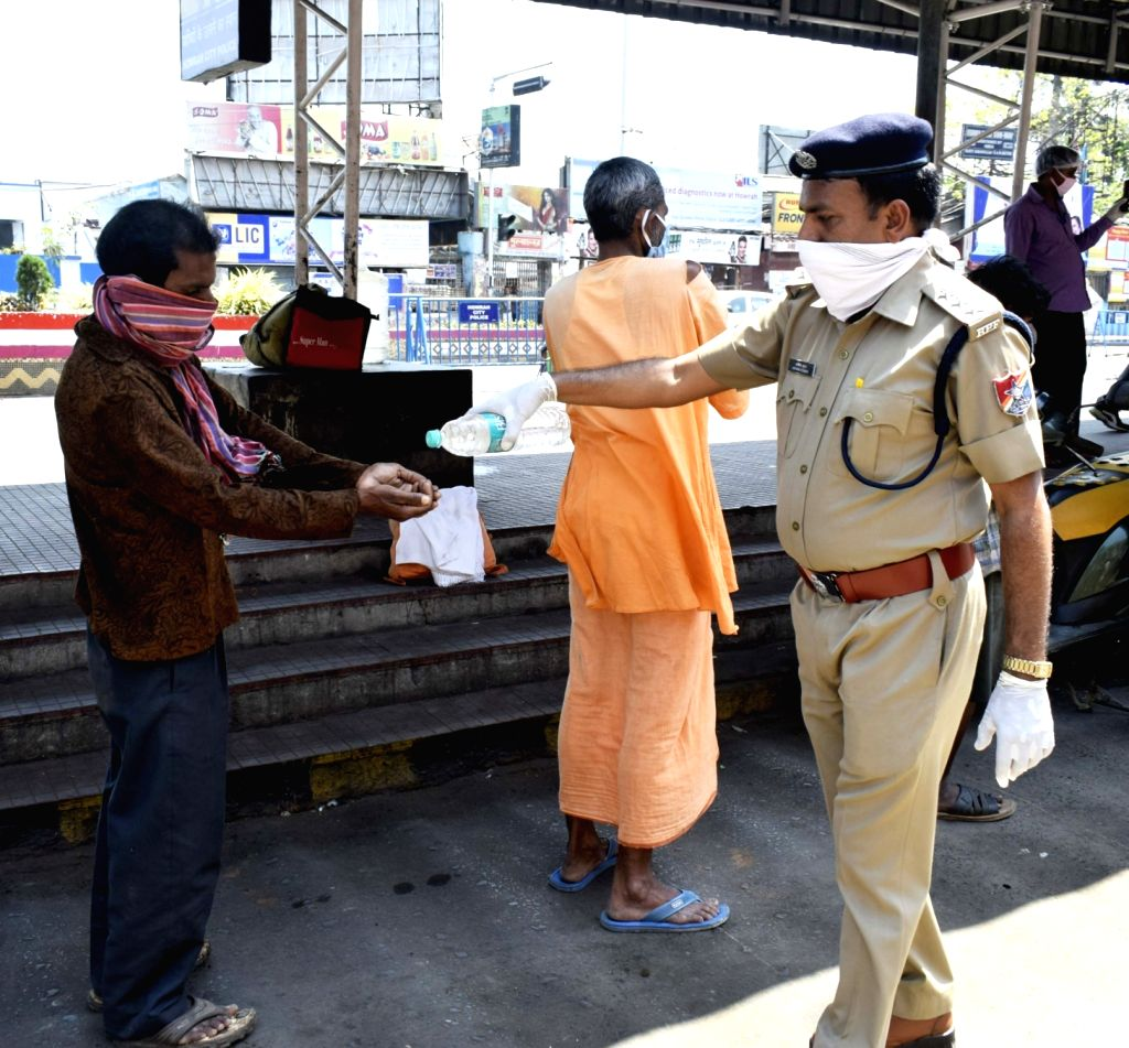 A Railway Protection Force (RPF) personnel helps a man wash his hands during food distribution for the poor, homeless and needy on Day 5 of the 21-day countrywide lockdown imposed to contain ...