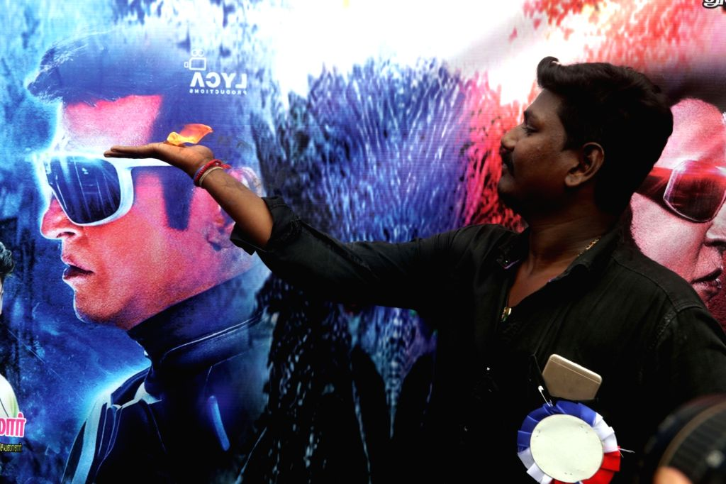 A Rajinikanth fan performs 'aarti' of the actor holding camphor in his hands outside a movie theater in Chennai, on Nov 29, 2018.