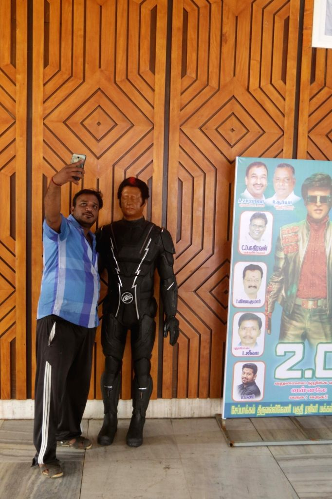 """A Rajinikanth fan poses for a selfie with his robotic model as he celebrates the release of """"2.0"""" in Chennai, on Nov 29, 2018."""