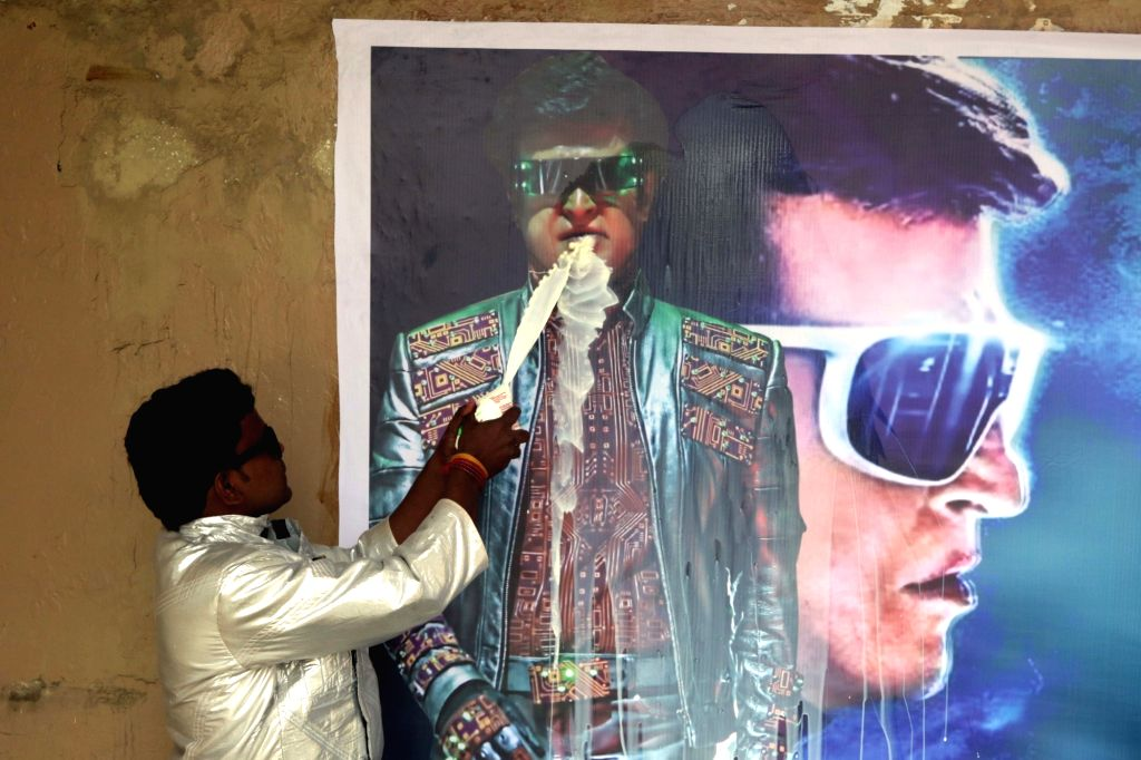 """A Rajinikanth fan washes the """"2.0"""" film poster as he celebrates the release of the film in Chennai, on Nov 29, 2018."""