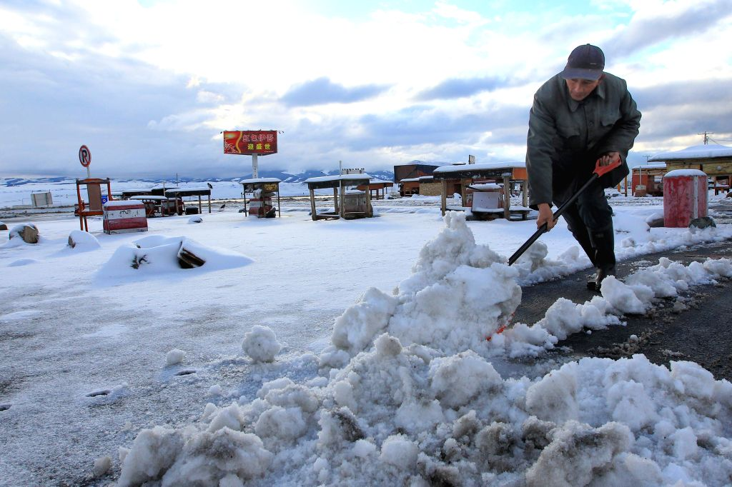 A rancher cleans snow on road on a grassland in northern Hami of Xinjiang Uygur Autonomous Region, Aug. 16, 2015. The mountainous Tianshan region saw an early snowfall ...
