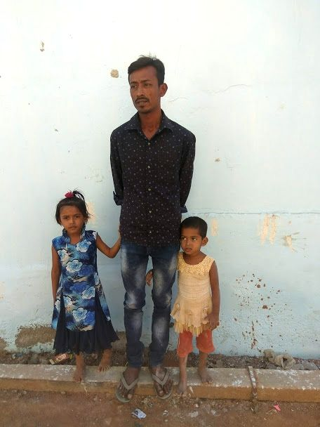 A refugee with his daughters, both born in India.