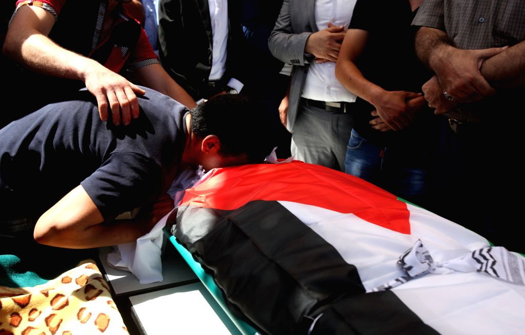 A relative of the Palestinian Sa'ed Dawabsha who died after being injured when his family house was set on fire by Jewish settlers on July 31, mourns over his body ...