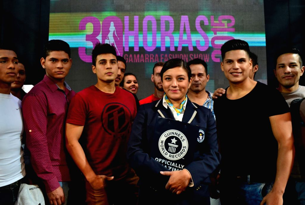 A representative of the Guiness World Records organization poses with participants during a fashion show held in a mall, in Lima, Peru, on August 4, 2015. According ...