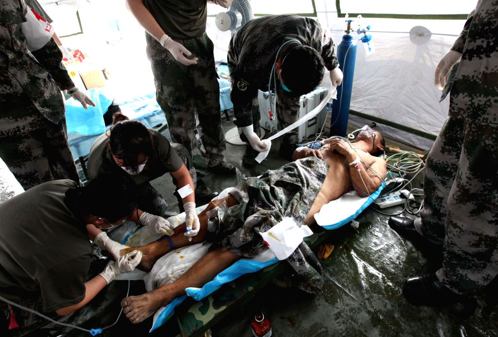 A rescued man receives medical treatment at a hospital of the People's Liberation Army in Tianjin, north China, Aug. 15, 2015. The man in his fifties was rescued ...
